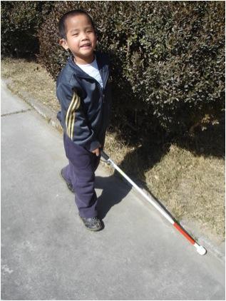 Anak laki-laki tunanetra berjalan dengan tongkat putih