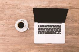 laptop di atas meja di sebelahnya ada secangkir kopi