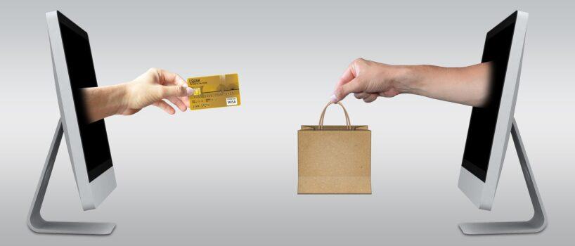 dua tangan keluar dari layar monitor. satu tangan menyerahkan kartu kredit, satu tangan lainnya menyerahkan sebuah paket belanjaan