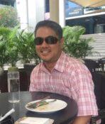 Jaka Ahmad duduk di balik meja, tersenyum ke arah kamera