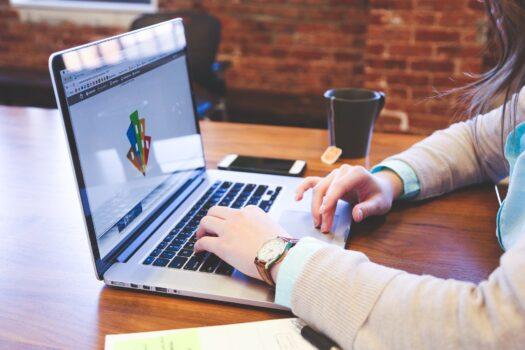 tangan seseorang sedang bekerja dengan laptop